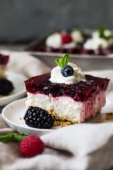 This Triple Berry Pretzel Salad is the perfect sweet and salty combo, with the salty pretzel crust, cream cheese middle, and fruity jello top! It's perfect at potlucks or family gatherings.