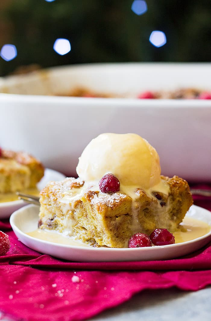 This Cranberry Bread Pudding with Whiskey Cream Sauce is the best way to use up day old bread! Rich brioche bread is baked in a cinnamon custard and drizzled with a whiskey cream sauce!
