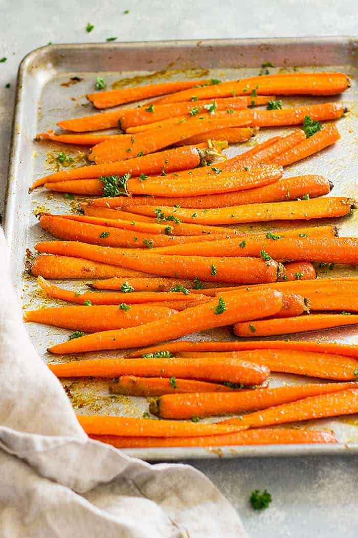 Honey garlic roasted carrots on a sheet pan garnished with parsley.