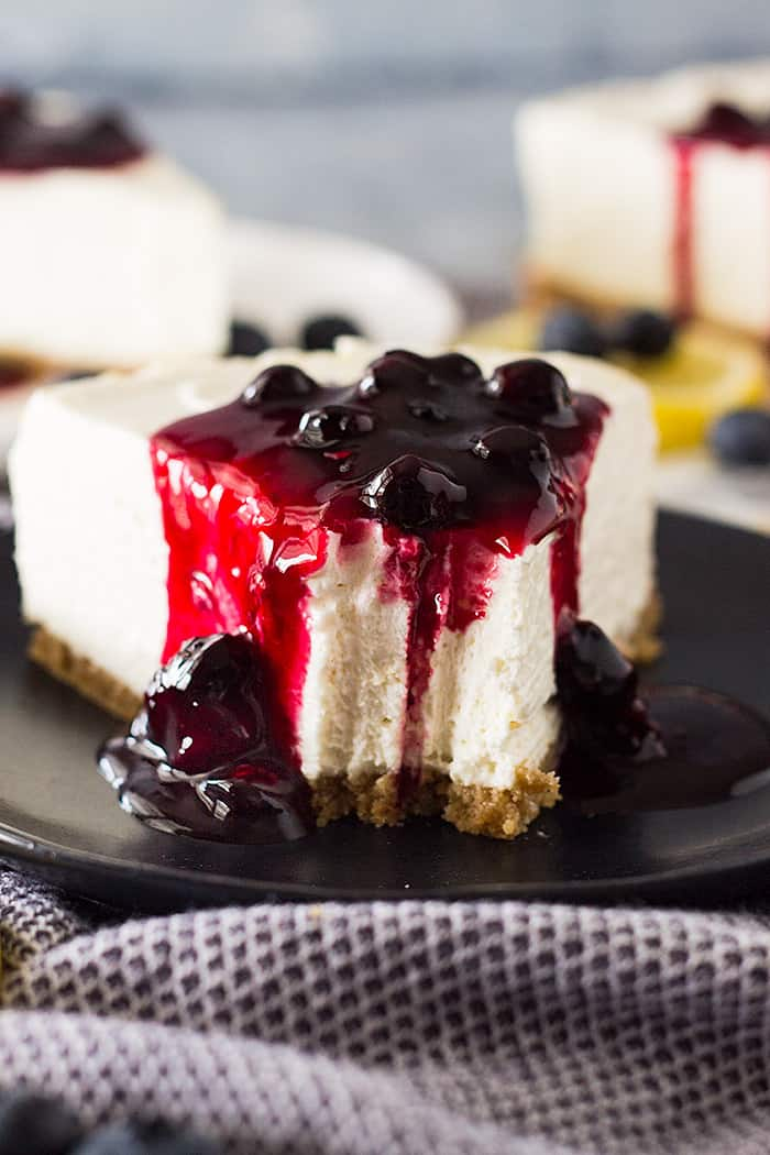 Slice of No Bake Lemon Blueberry Cheesecake with a bite taken out.