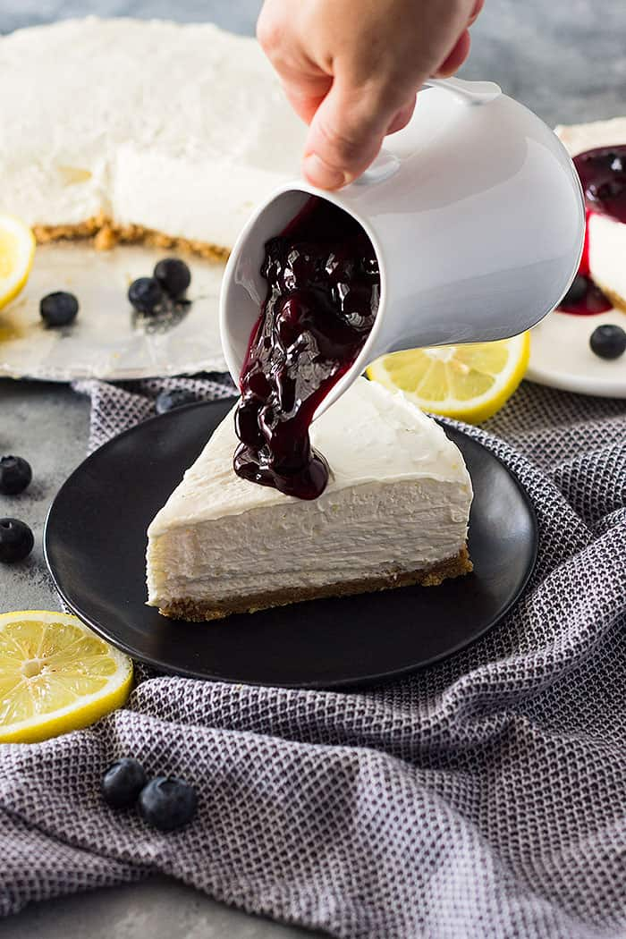Slice of No Bake Lemon Blueberry Cheesecake with blueberry topping being poured on top.