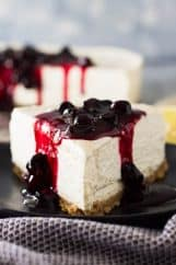 Close up of a slice of No Bake Lemon Blueberry Cheesecake with blueberry sauce on top.