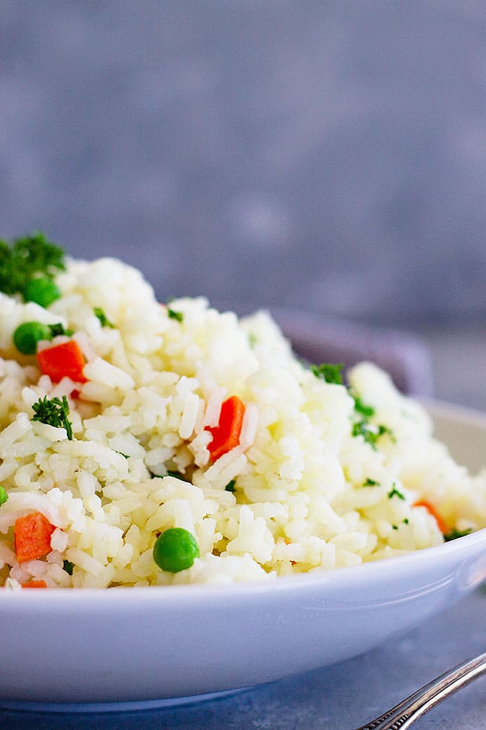 This Easy Rice Pilaf with Carrots and Peas is a staple recipe everyone should learn! It goes great with so many dishes and is so easy to make!