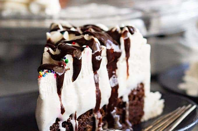 This Brownie Ice Cream Cake is an easy way to impress your guests. Chewy brownie on the bottom, topped with hot fudge sauce, vanilla ice cream, and a homemade whipped cream topping. #brownie #icecream #cake