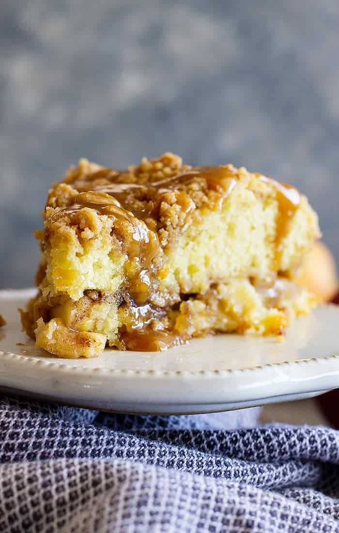 This Apple Crumb Cake is the perfect fall treat! It's filled with spiced apples, an extra thick crumb layer, and a tender cake. Drizzle with an easy homemade caramel sauce for the perfect treat! #apple #cakerecipes #easyrecipe #applecake