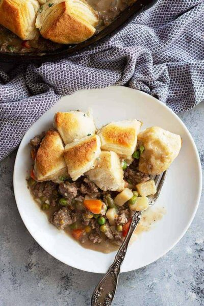 This easy Skillet Beef Pot Pie will please the whole family. It's filled with ground beef and vegetables in an easy homemade gravy. Top with store bought or homemade biscuits for the ultimate comfort food! #potpie #groundbeef #easyrecipe #beefpotpie