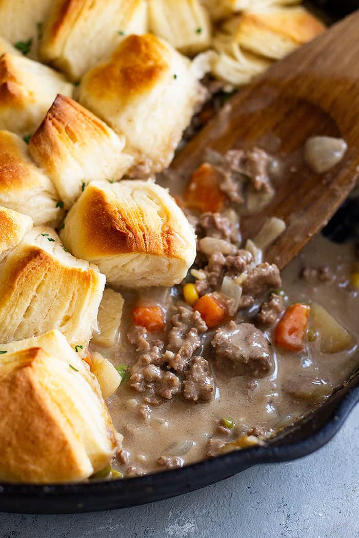 This Easy Skillet Beef Pot Pie Recipe is the ultimate comfort food made easy! It's filled with vegetables in an easy homemade gravy and topped with biscuits. #potpie #groundbeef #easyrecipe #beefpotpie