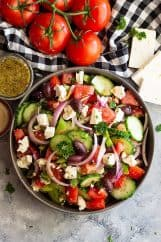 Greek Salad is a quick and simple salad that's full of flavor and crunch. Greek Salad Ingredients are bright fresh and delicious. Pair this salad with leftover rotisserie chicken or seafood for a delicious and healthy meal! #greeksalad #healthysalad