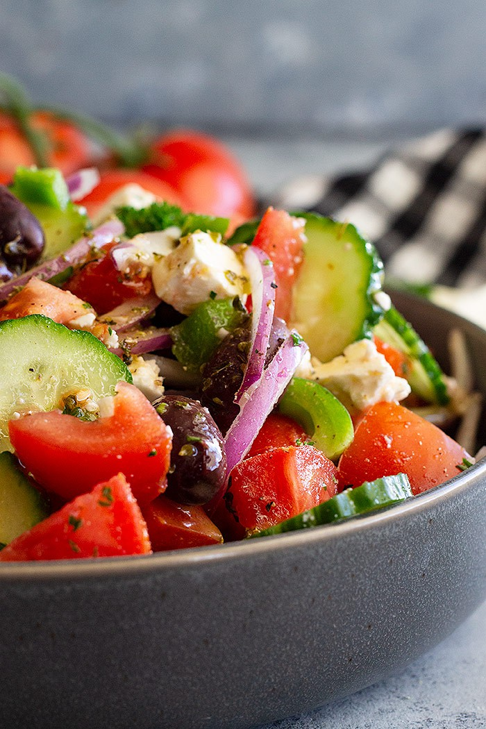 This Easy Greek Salad is perfect for those looking for something healthy to eat other than spinach or kale!! It has a quick and easy homemade dressing and can easily be paired with cooked chicken or seafood! #greeksalad #healthysalad