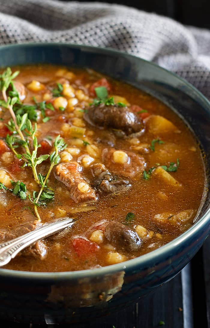 A bowl of comforting beef and barley soup garnished with fresh thyme.