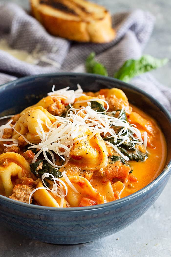 A bowl of tortellini soup in a blue bowl topped with cheese.