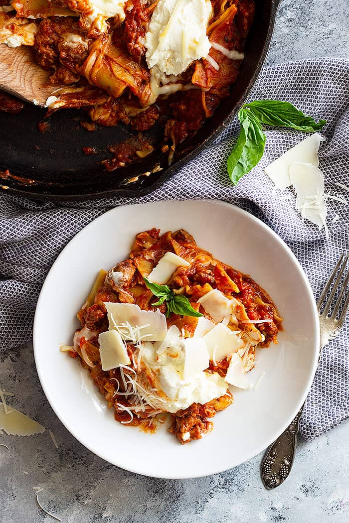 This easy Skillet Lasagna Recipe is pure comfort food made easier! No time to boil noodles and layer noodles, then this skillet lasagna will make the perfect weeknight meal! #onepotmeal #skilletlasagna