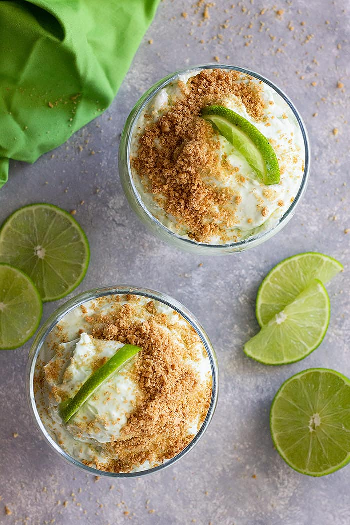 A top down view of lime cheesecake fluff in dessert bowl. Garnished with limes and graham cracker crumbs.
