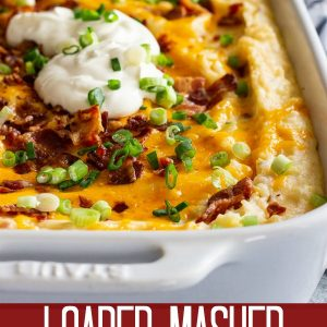 This Loaded Mashed Potato Casserole is the perfect make ahead side dish! It's filled with bacon and cheese and feeds a crowd! #loadedpotatoes #mashedpotatoes
