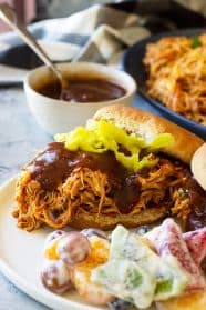 Close up picture of slow cooker bbq chicken on a bun with bbq sauce.