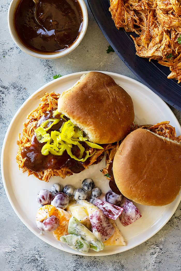 Plate of slow cooker bbq chicken sandwiches with bbq sauce.