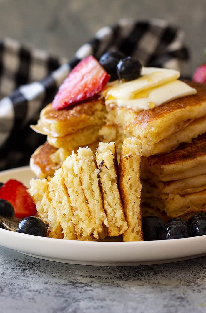 A fork stacked with a big bite of fluffy buttermilk pancakes ready to be eaten.