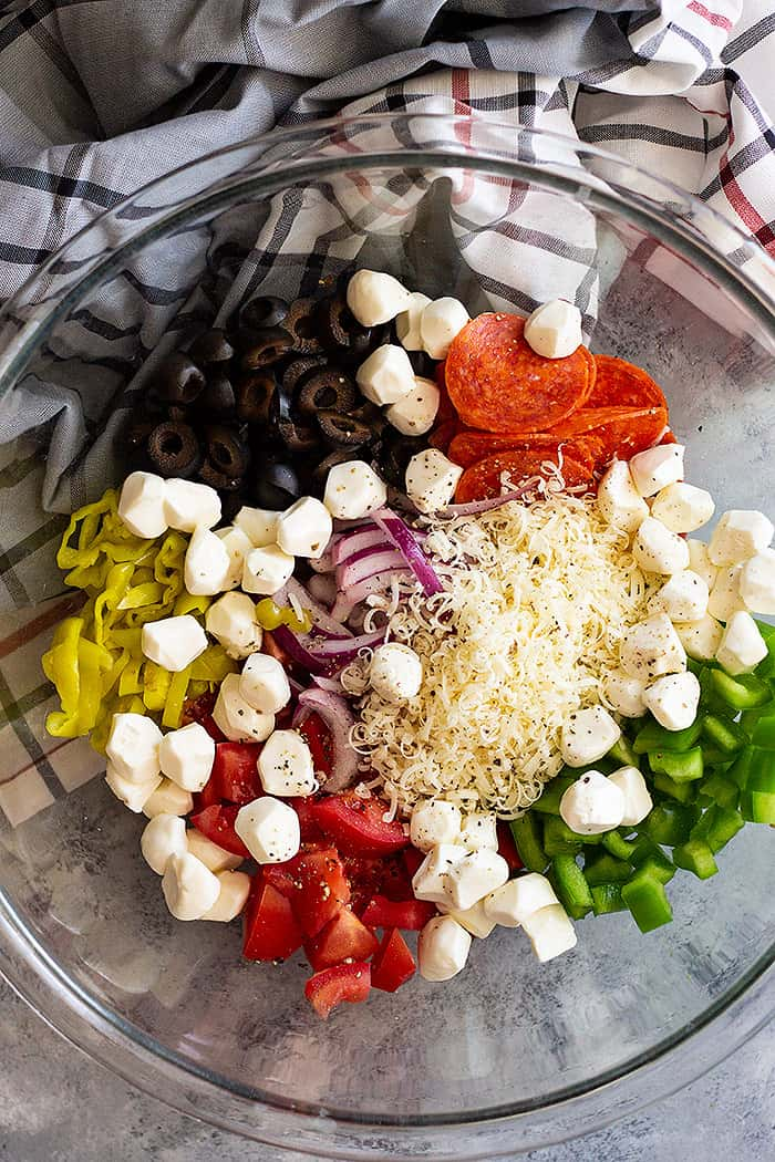 A large bowl with Pepperoni Pasta Salad ingredients arranged in groups. Getting ready to mix the salad together.
