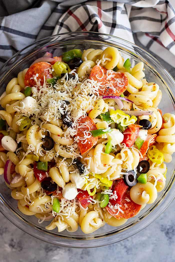 A huge bowl of Pepperoni Pasta Salad topped with Parmesan cheese.