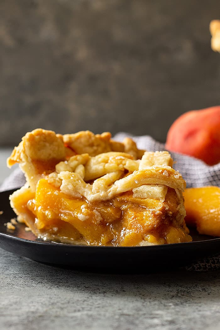 A slice of peach pie with an all butter crust.