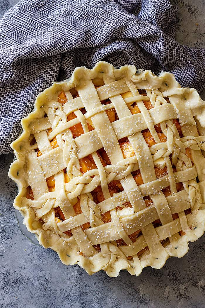 Top down view of a peach pie with an all butter crust lattice top.