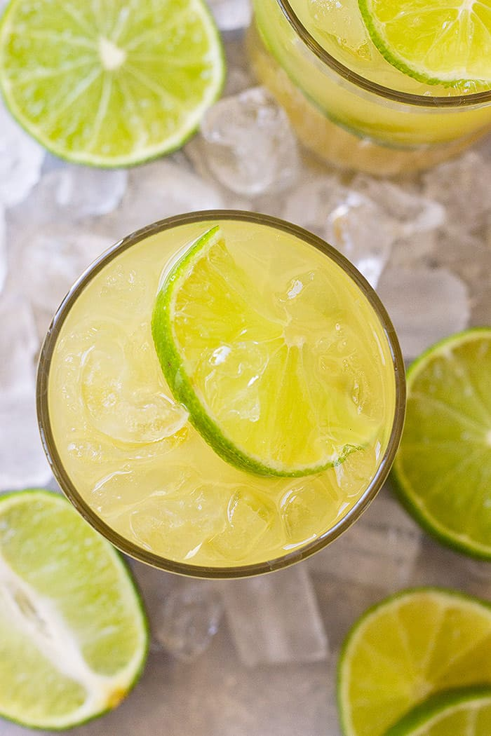 Top down view of classic margarita in a glass with a lime wedge and lots of ice.
