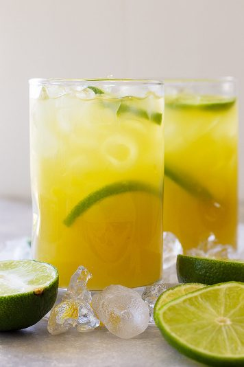 Tall glass of classic margarita with lime wedges and ice.