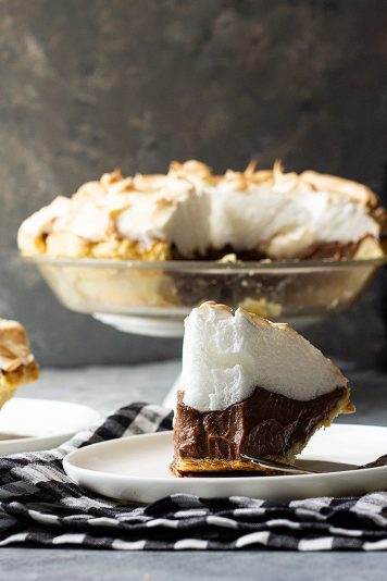 Slice of chocolate meringue pie on a plate with a bite taken out.