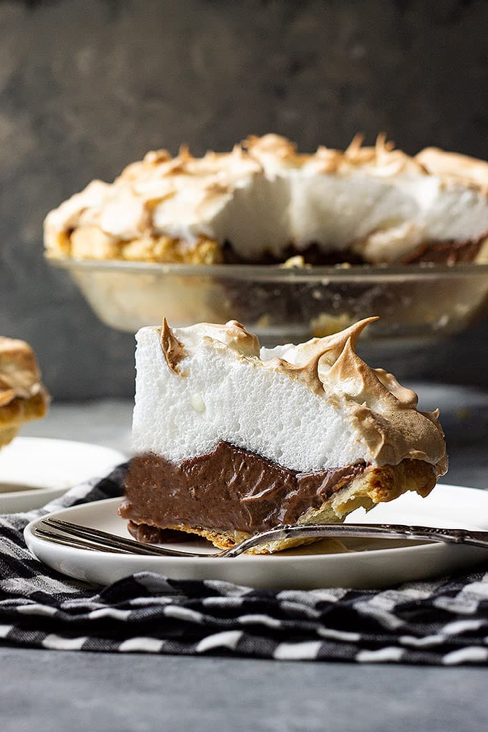 Large slice of chocolate meringue pie on a plate with a fork.