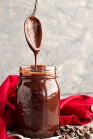 A spoon pulled straight up from a jar of homemade hot fudge sauce letting it drizzle back into the jar.