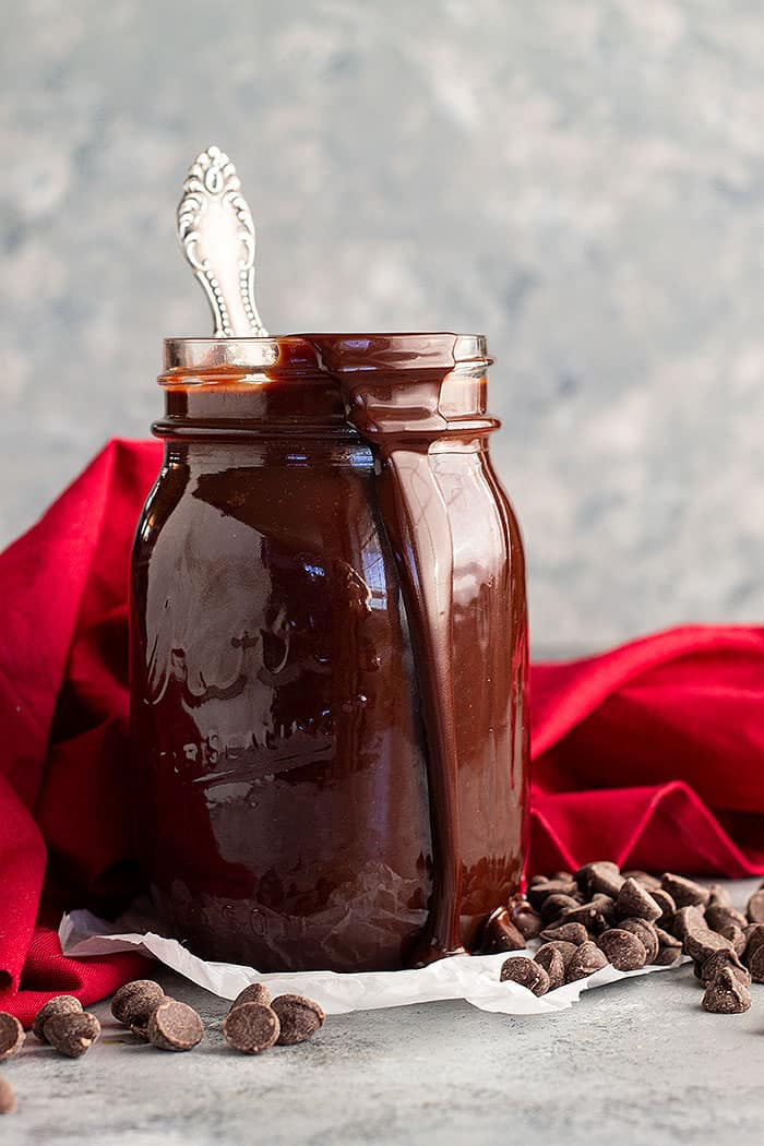 A jar of hot fudge sauce with a spoon in it and a drip of sauce going down the side of the jar.