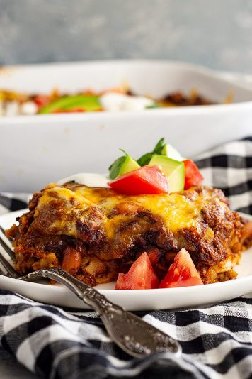 A slice of Mexican Casserole on a white plate with a fork.