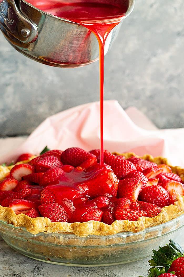 Pouring strawberry jello filling over the pie.
