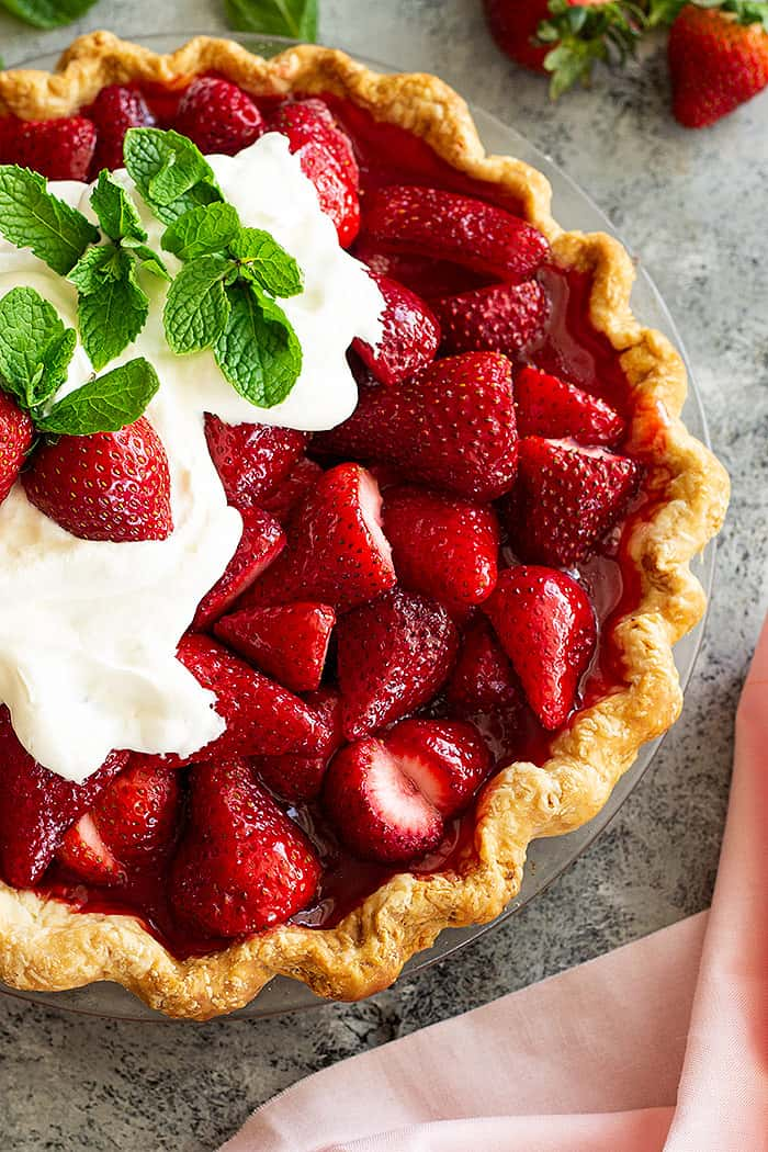 Top down view of strawberry pie topped with freshly whipped cream and mint.