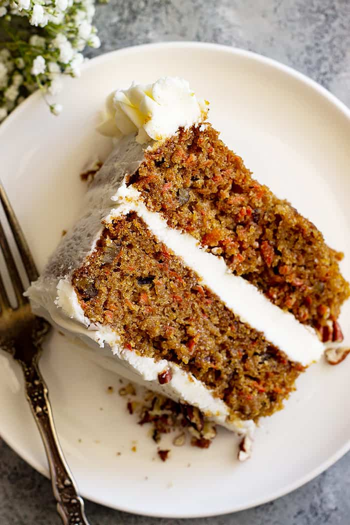 Top down view of slice of carrot cake on a white plate.