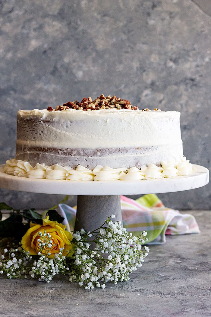 Carrot cake on a cake stand decorated with chopped pecans and baby's breath.