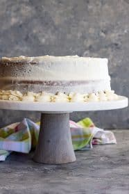A cake on a stand covered in cream cheese frosting.
