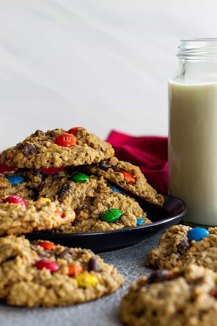 Monster cookies on a plate with a glass of milk.
