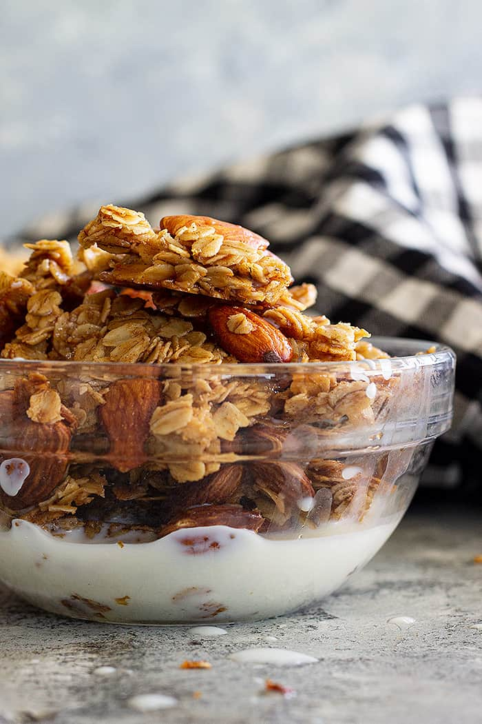 A bowl of honey almond granola with a splash of milk.