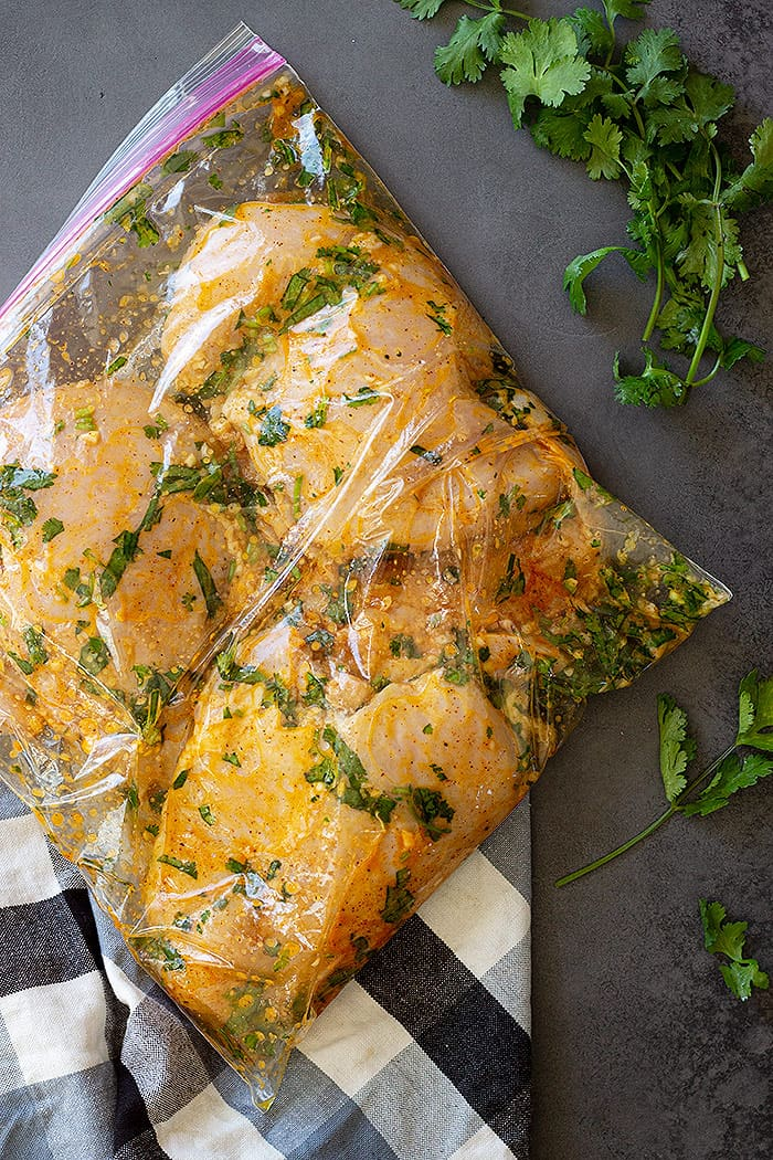 Chicken marinating in a bag.