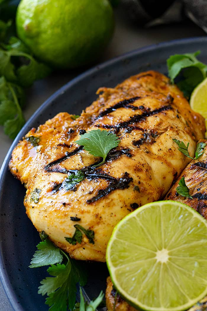 Grilled chicken on a blue plate garnished with lime and cilantro.