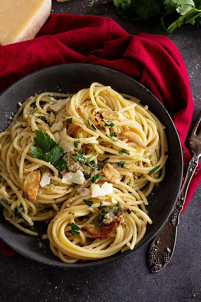 Top down view of spaghetti in a dark bowl and garnished with parmesan and parsley.