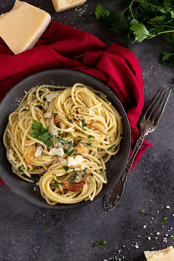 Pasta in a dish garnished with extra cheese and parsley.