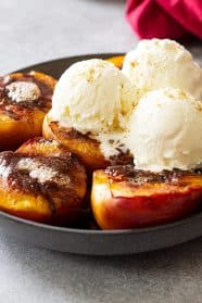 Grilled peaches topped with vanilla ice cream.