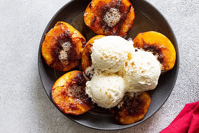 Top down of grilled peaches topped with ice cream.