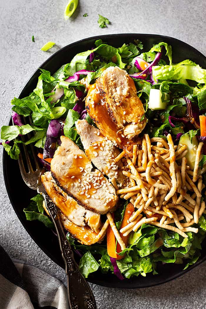 Top down view of salad drizzled with Asian dressing and sprinkled with sesame seeds and crunchy chow mein noodles.