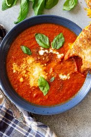 Top down view of a bowl of tomato soup garnished with basil, parmesan cheese, and swirl of cream, and a grilled cheese off to the side.