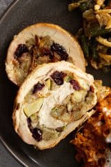 A close up view of the sliced turkey breast on a plate. You can see the stuffing with the apples and dried cranberries swirled in the turkey.