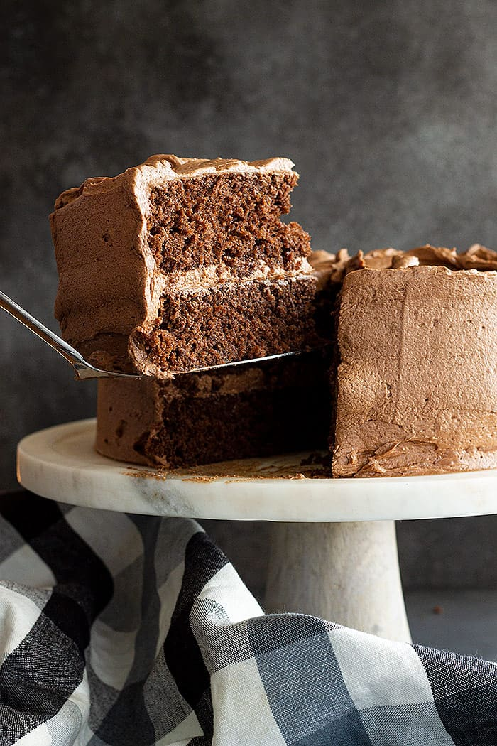 A large slice of chocolate cake with a smooth chocolate frosting is being lifted from the cake.