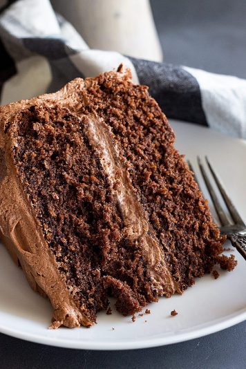 A close up of a slice of delicious moist chocolate cake with chocolate frosting.